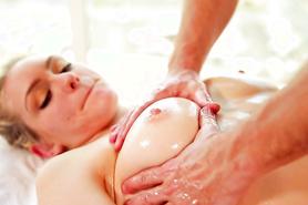 Делает эротический массаж обнаженной блондинке