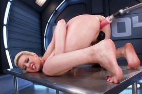 Стройная блондинка после работы развлекается с секс машиной стоя раком